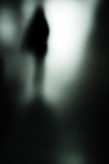 Defocused image of silhouette people standing against blurred background