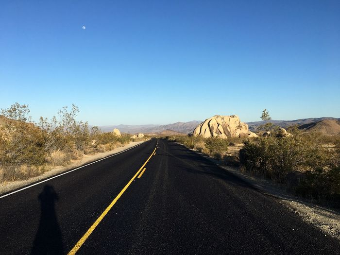 Road leading towards mountain against clear sky