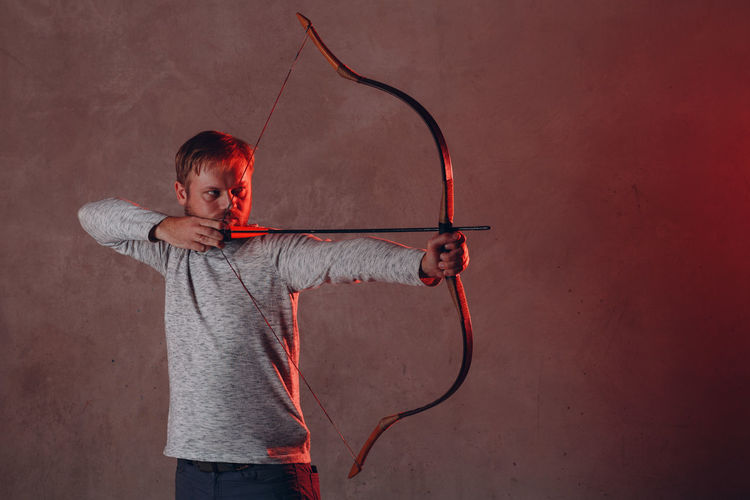 Man holding bow against wall