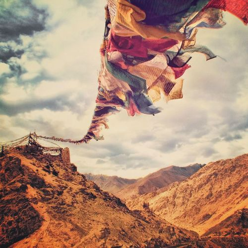 Prayer flags in mountains against cloudy sky