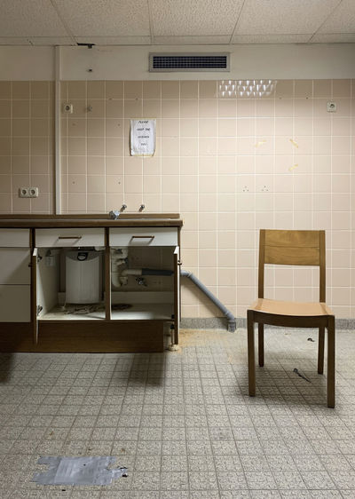 Empty tables and chairs against wall