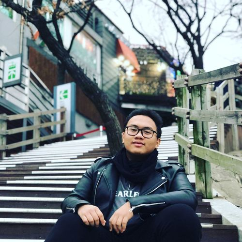 Portrait of man sitting on steps in city