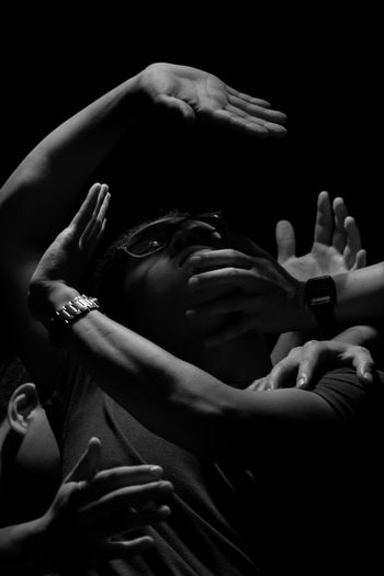 Cropped hands covering man face over black background