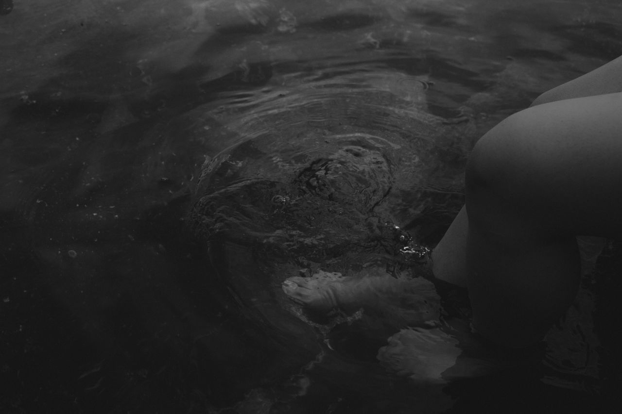 CLOSE-UP LOW SECTION OF WOMAN STANDING IN WATER