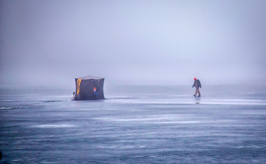 Beauty In Nature Day Fog Full Length Horizon Over Water Ice Fishing Ice Fishing Huts In Background Leisure Activity Lifestyles Men Nature One Person Outdoors People Real People Scenics Sea Sky Water Waterfront Wave