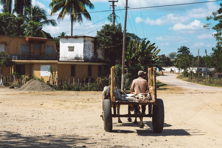 Man sitting on seat by road against building