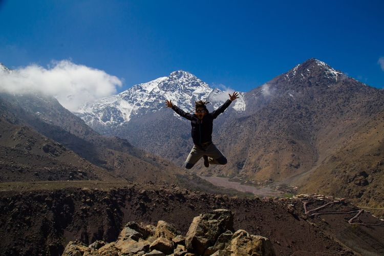 Playful man jumping against mountains during winter