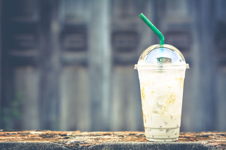 Close-Up Of Fresh Drink In Disposable Cup On Retaining Wall