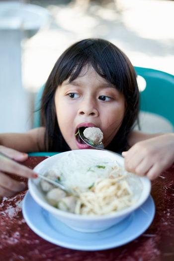 Cute girl eating food in bowl at home