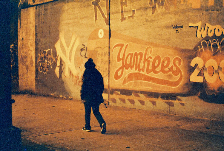 Pedestrian walking in front of graffitied wall at night