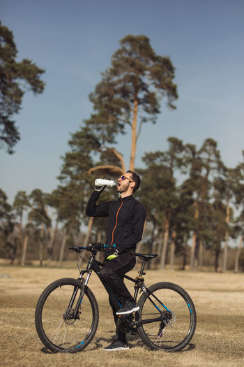 Man riding bicycle against trees