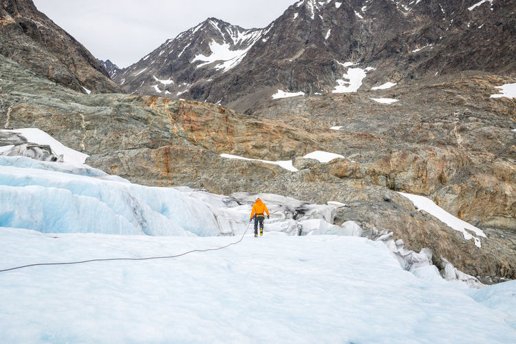 Rear View Of Person Hiking On Glacier Against Mountain