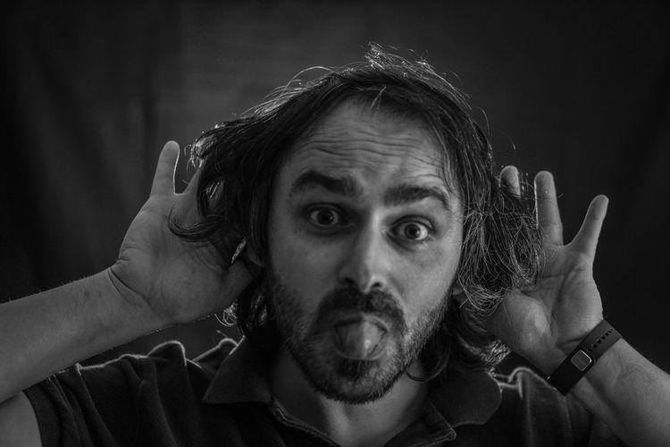 Portrait of mischievous man teasing against wall