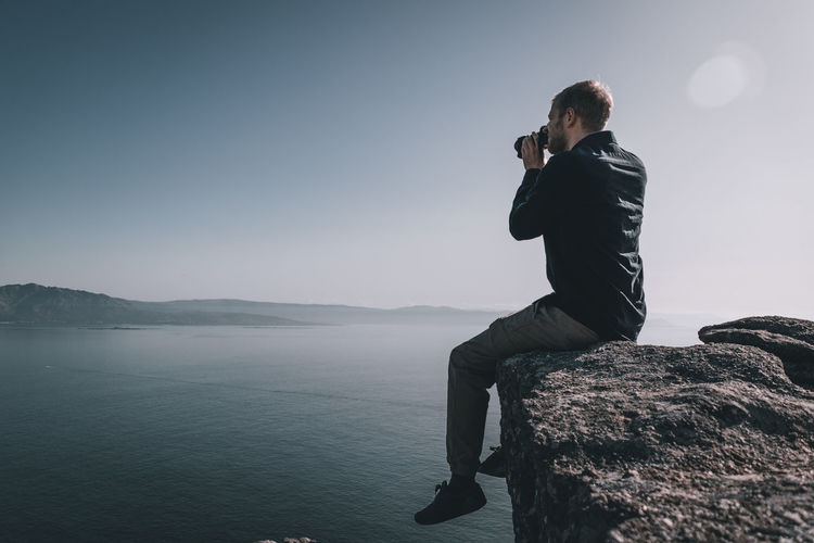 Man sitting on rock looking at sea and mountain with binoculars against sky
