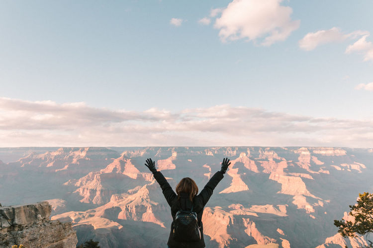 Rear view of female hiker with arms raised at grand canyon national park against sky