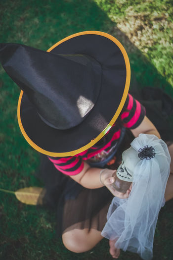 High angle view of woman wearing witch hat holding human skull while sitting on field in park