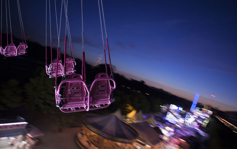 Chain swing ride spinning against sky at dusk