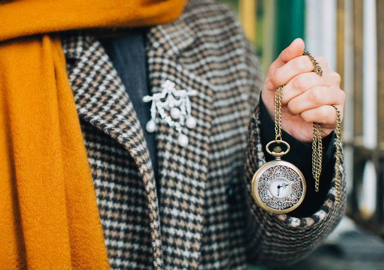 Midsection of person holding pocket watch