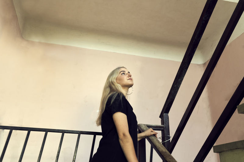 Young woman looking away while standing on railing against wall