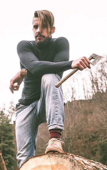 Low angle view of young man with axe standing on log
