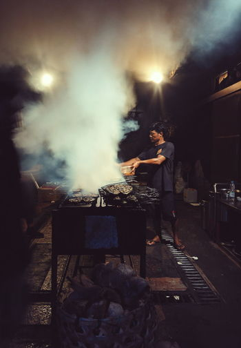 People on barbecue grill at night