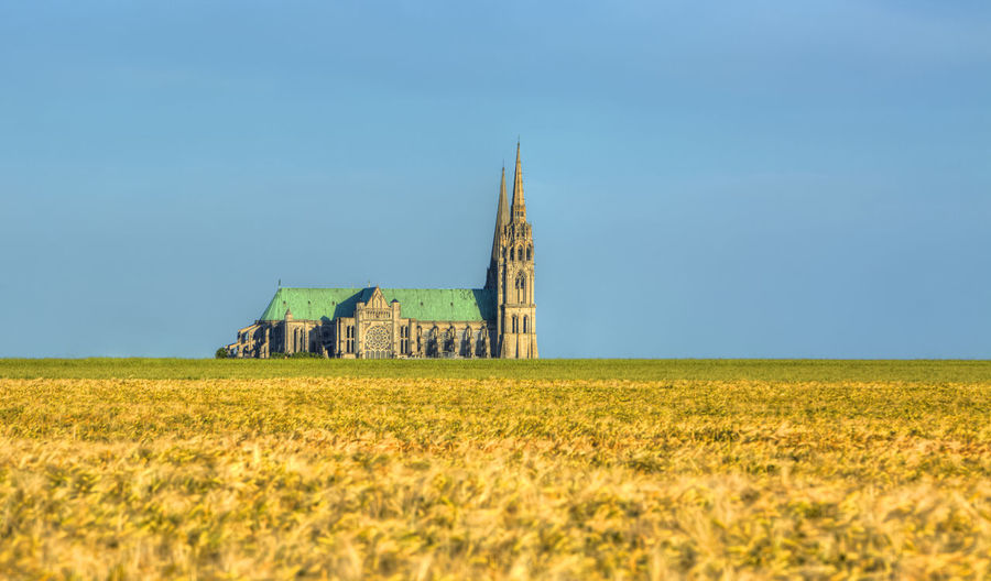 Image of the Cathedral of Our Lady of Chartres seen from outside of the city above the fields of cereals which surround the locality.This is a very famous Gothic cathedral which contains original stained glass from the 13th century. Sky Landscape Field Built Structure Land Architecture Plant Environment Building Exterior Building No People Nature Outdoors Cathedral Chartres Chartres, France Chartres Cathedral Field Cereals Summer Summertime Rural Scene Horizon Over Land Landmark Landmark Building France Beauce History Clear Sky Religion