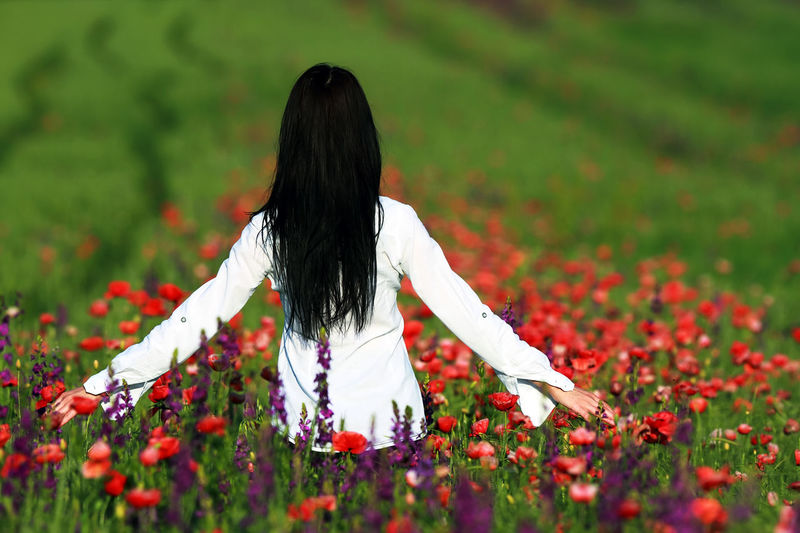 Rear view of woman with red flower on field