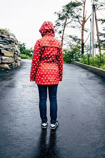 Rear view of woman standing on road
