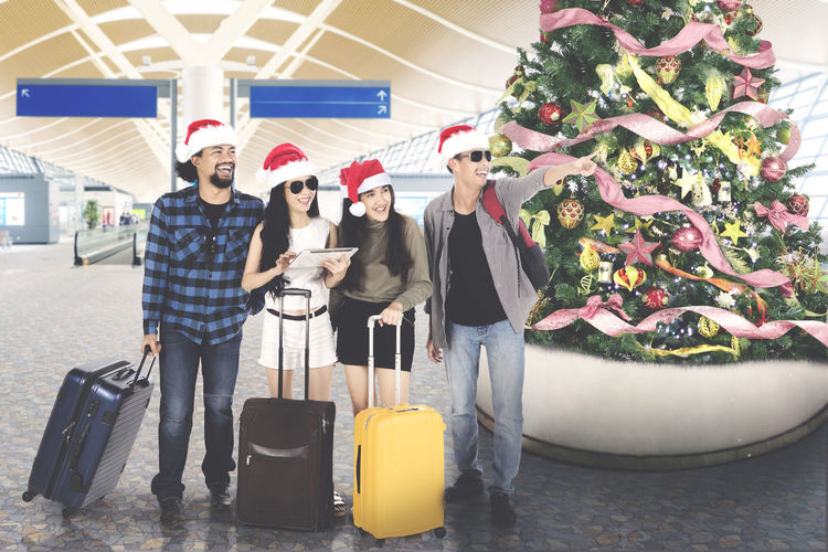 Friends standing at airport during christmas