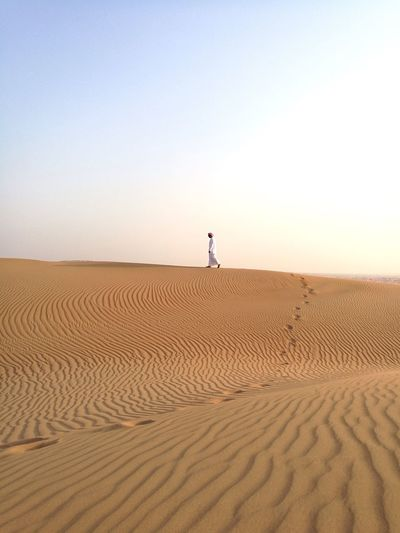 Man walking on sand dune against clear sky