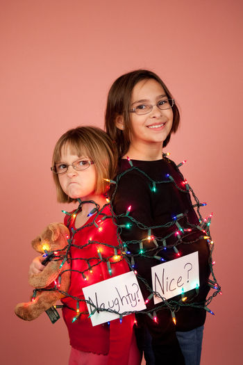 Naughty and nice Christmas concept shot of two young sisters wrapped in Christmas lights Christmas Christmas Lights Child Childhood Colored Background Emotion Full Frame Funny Concept Naughty And Nice Naughty Girl  Nice Sister Smiling