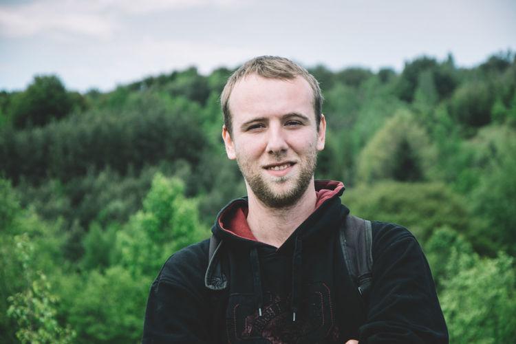 Portrait of smiling man against trees