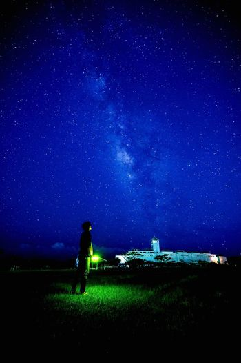 Man Standing On Landscape Against Starry Blue Sky
