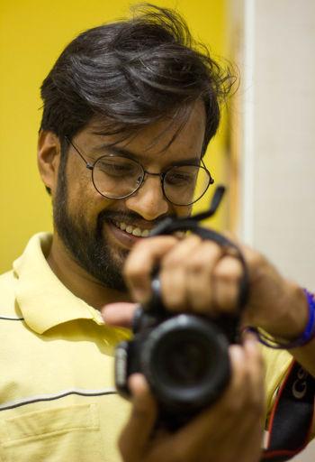 Portrait of smiling man holding eyeglasses