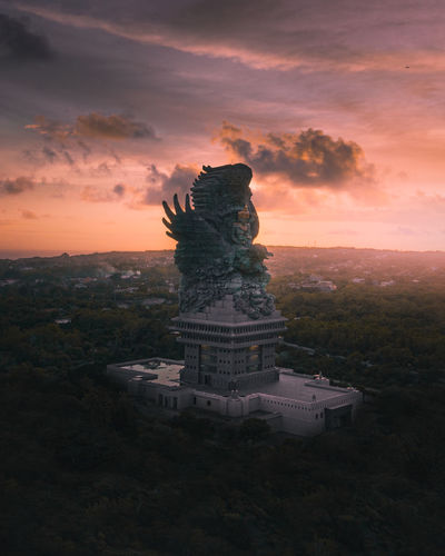 Statue in city against sky during sunset