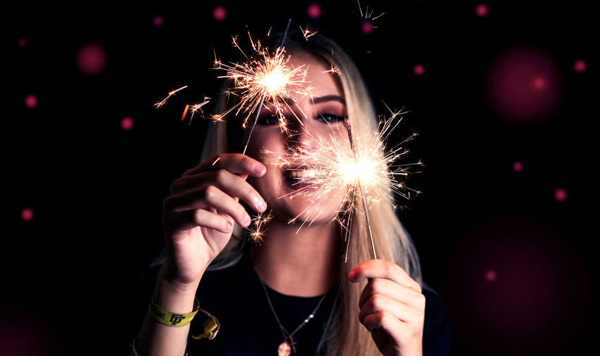 Close-up of woman holding sparkler at night
