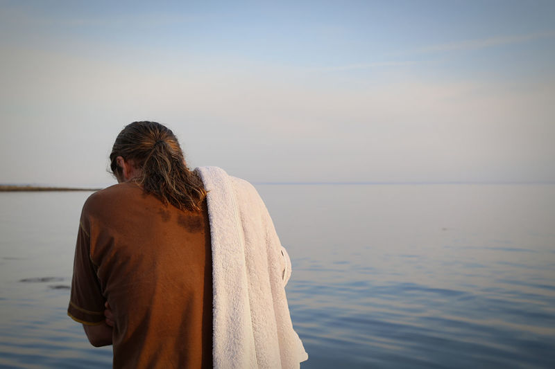 Rear view of man standing with towel by sea against sky