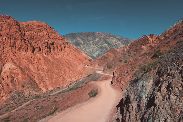 Dusty road with colorful mountains in purmamarca, argentina.