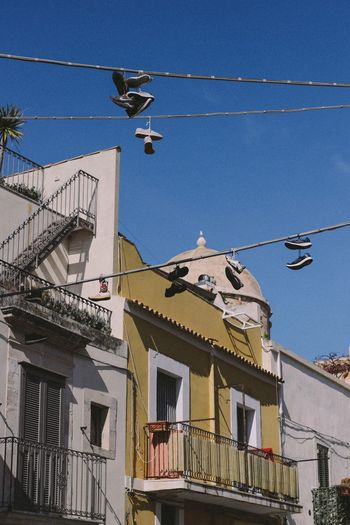 Architecture Cable Low Angle View Built Structure Building Exterior Residential Building Day Outdoors No People Sky Sicilia Siracusa Shoes Shoes On A Wire Wire