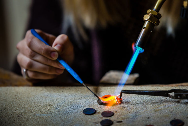 Art And Craft Human Hand Craft Focus On Foreground Close-up Hand Making Preparation  One Person Indoors  Holding Blue Workshop Creativity Welding Jewelry Jewelry Making Craftsman Working Craftsmanship  Flame Melting