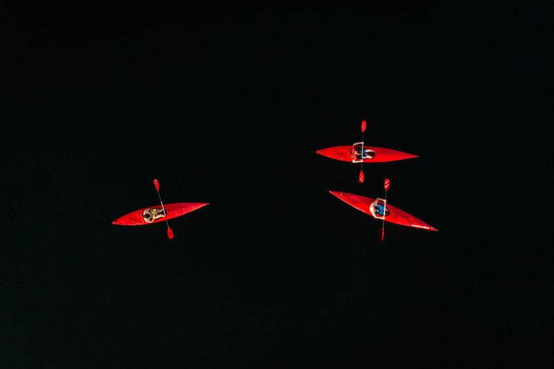 Red airplane flying against sky at night