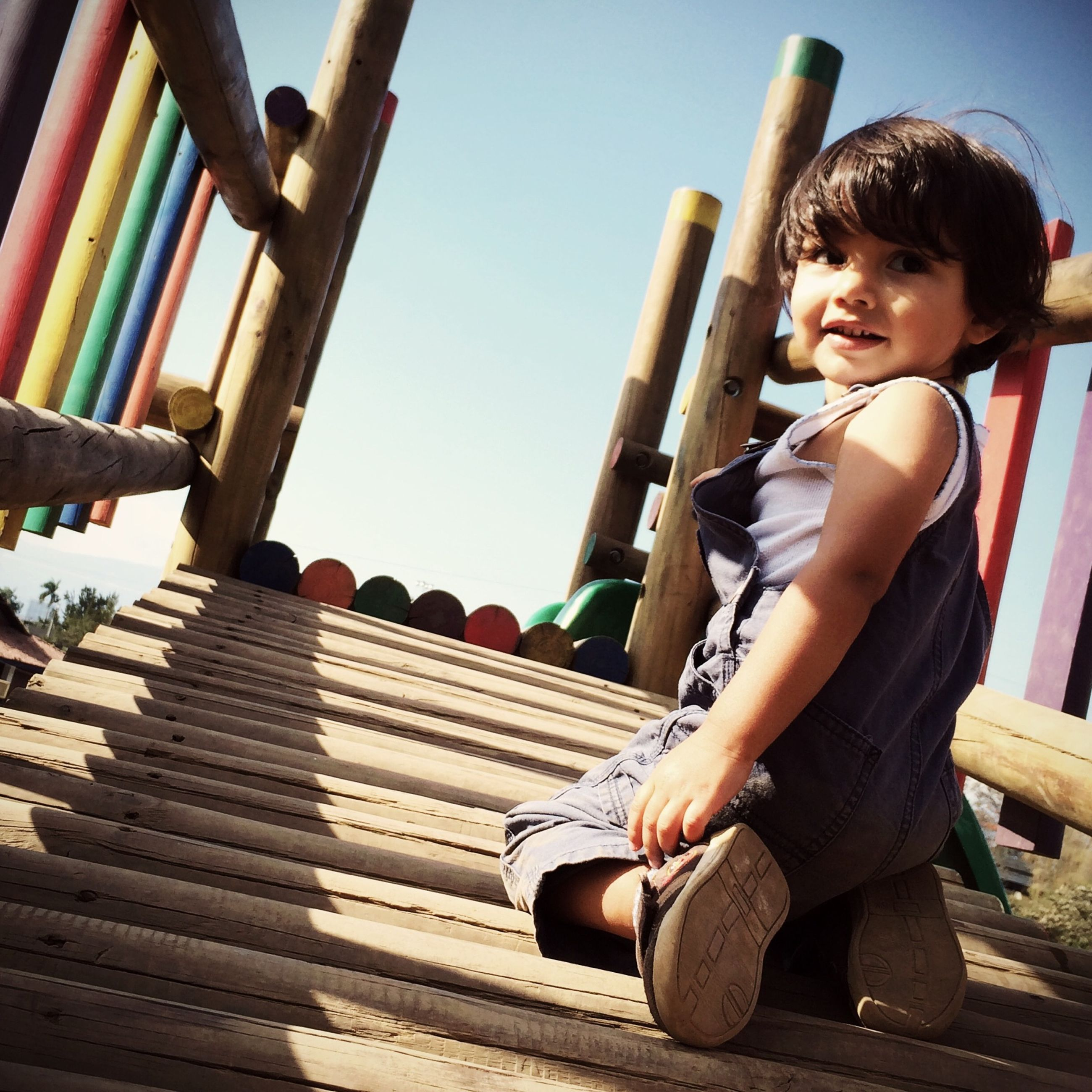 lifestyles, leisure activity, steps, full length, person, casual clothing, railing, childhood, wood - material, young adult, low angle view, sitting, built structure, steps and staircases, staircase, sunlight, day, outdoors