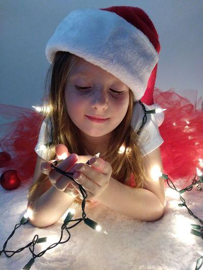 Close-up of girl holding illuminated string lights