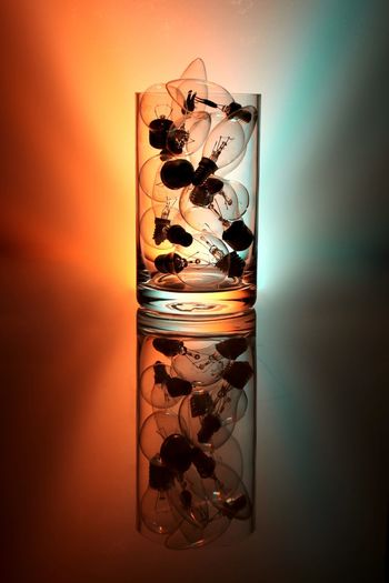 Electric bulb in drinking glass against colored background