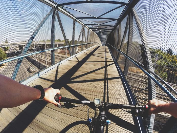 Cropped Image Of Man Riding Bicycle On Bridge