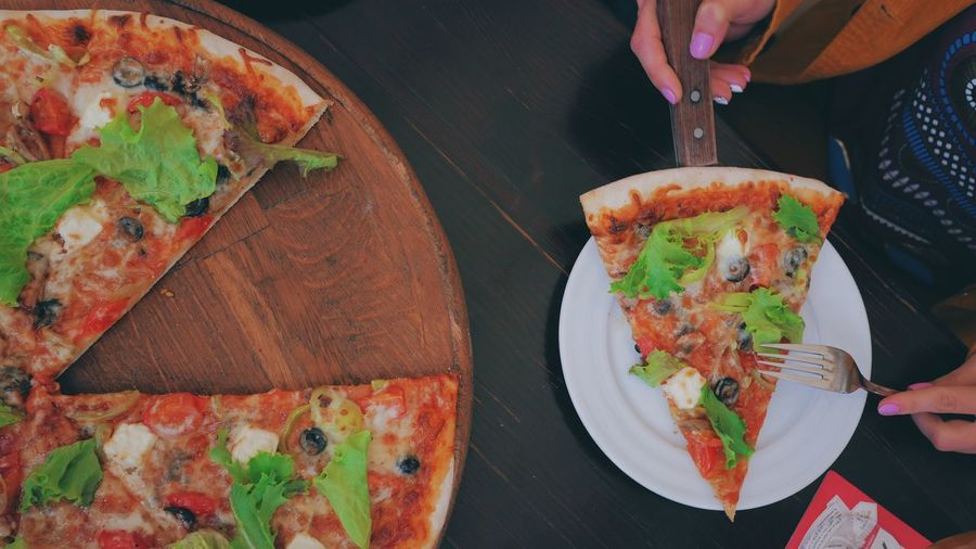 Cropped hand of woman holding pizza on table