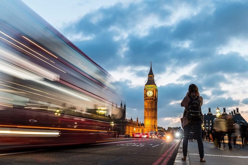 Rear view of woman standing on sidewalk by bus and big ben against cloudy sky during sunset