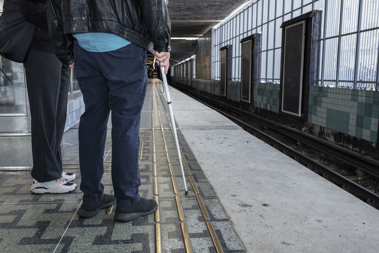 Low section of people standing on railroad station platform