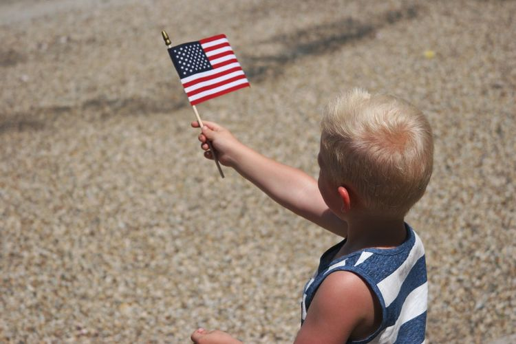 High Angle View Of Boy Holding American Flag