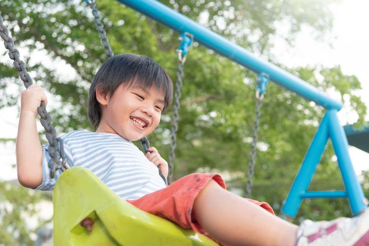 Boy playing on slide at playground